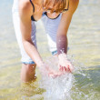 Female Traveler Playing In Shallow Water - Stock Photo