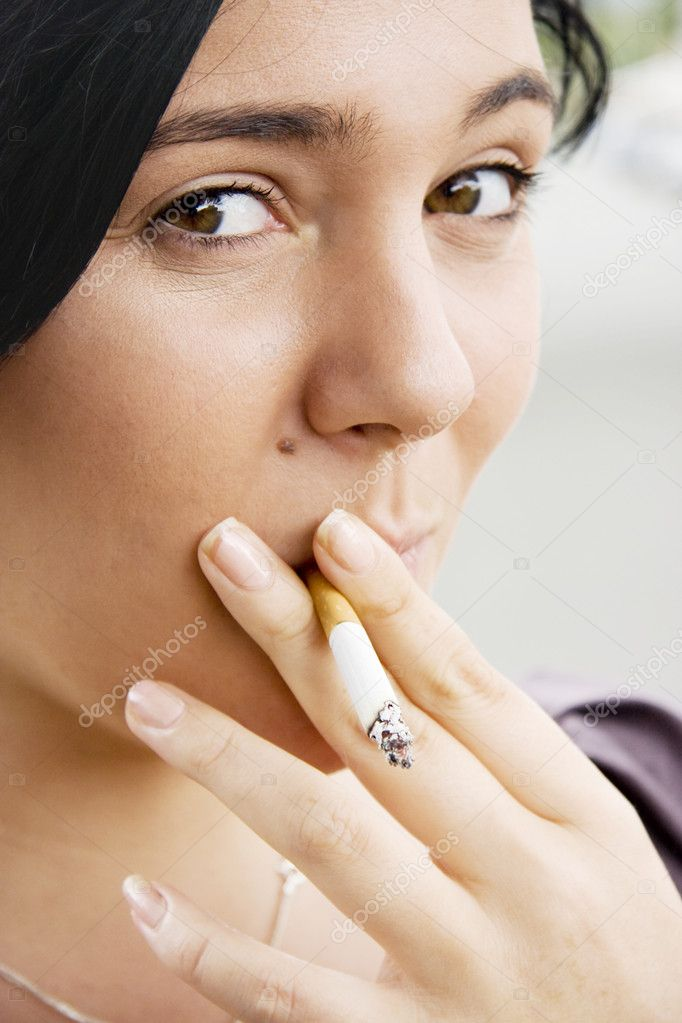 Young Woman Inhaling Smoke From A Lit Cigarette With A Mischievous Look Of Guilt — Stock Photo #10317501