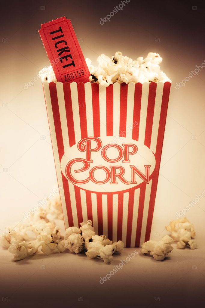 Depiction Of The Fifties Cinema Era With A Vintage Red Striped Old Popcorn Box Overflowing With Buttered Popcorn Coupled With A Movie Ticket  Stock Photo #10317656