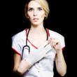 Serious young nurse removing her latex gloves — Foto Stock