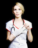 Serious young nurse removing her latex gloves — Stock Photo