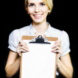 Smiling enthusiastic woman holding blank clipboard — Stockfoto