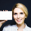 Young woman holding up a blank card — Stockfoto
