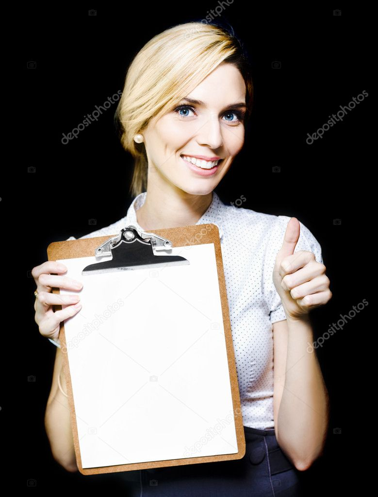 Beautiful stylish enthusiastic woman with a lovely wide smile holding a blank clipboard and giving a thumbs up gesture of approval and recommendation — Stock Photo #10412699