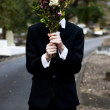 Burying Face In Funeral Flowers - Stock Photo