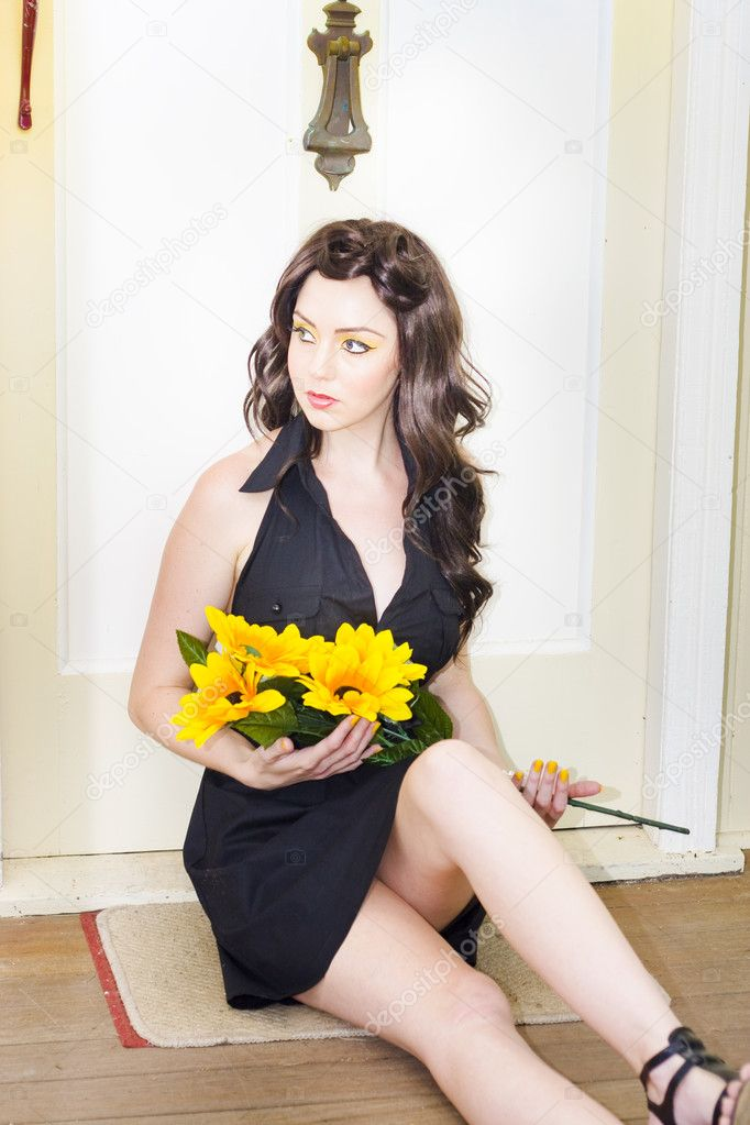 A Sad And Lonely Woman Locked Out In The Cold Sits In Solitude By A Front Door Holding Floral Sunflowers Waiting For Someone To Open The Door, In Romanic Hope — Stock Photo #10588350