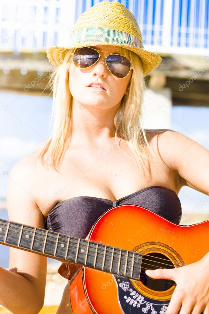 Sexy And Beautiful Young Woman Holding Guitar While Wearing Hot Summer Fashion Standing On A Tropical Paradise Holiday Beach In Sun Shades, Music Concept — Stock Photo #10589134