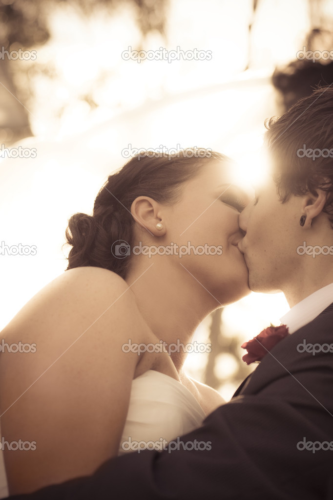 Young Happy Newlyweds Kiss Showing Their Undying Love And Devotion To One Another With Shining Sunlight In The Background — Stock Photo #10589493