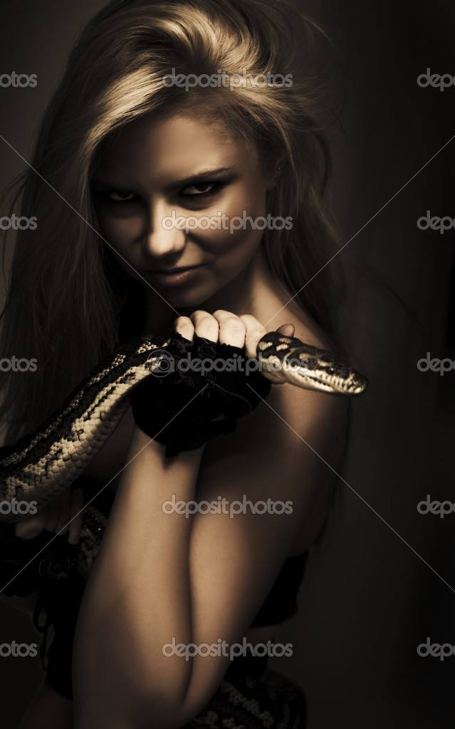 Dark moody portrait of a mysterious blonde sorceress holding the head of a python in her hand — Stock Photo #9719472