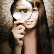 Beautiful female watching through magnifying glass - Foto Stock