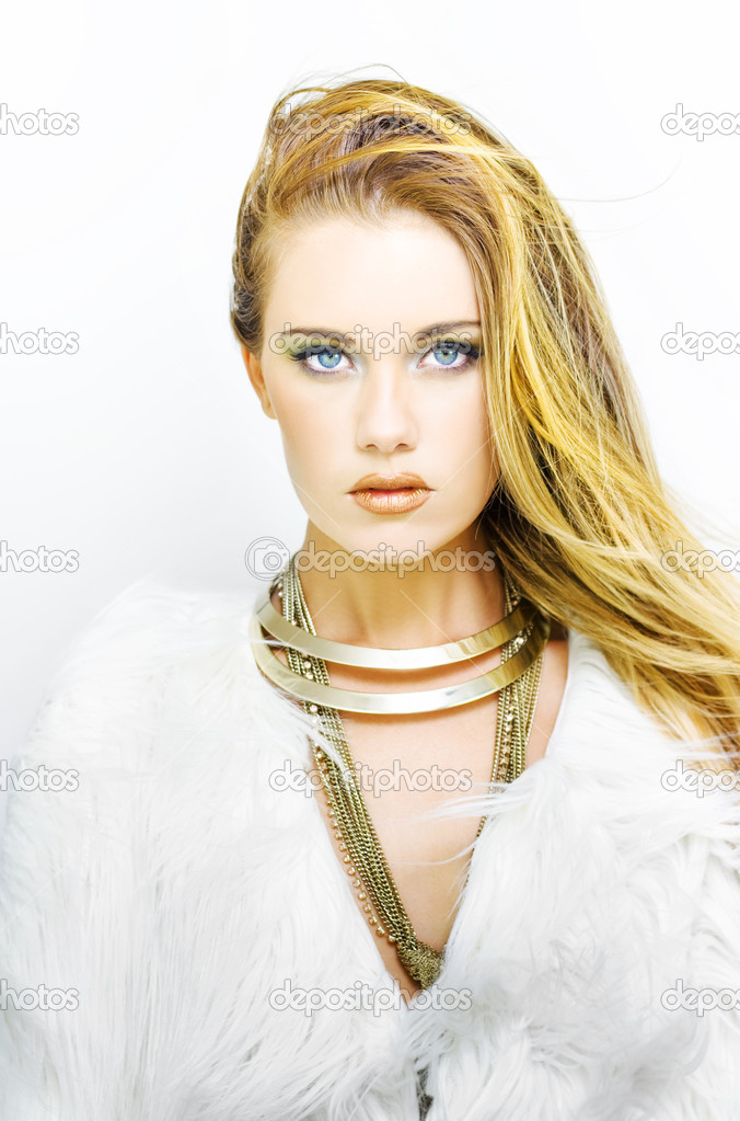 Beautiful woman with clean fresh skin wearing gold necklace and furry coat looking straight at the camera on a white background in a makeup and cosmetics conceptual  Stock Photo #9726017