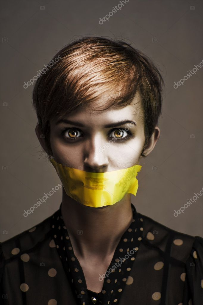 Dark Headshot Of A Distressed And Oppressed Woman Bound And Gagged In Silence With Yellow Masking Tape Covering Her Mouth In A Speak No Evil Conceptual  Stock Photo #9727556