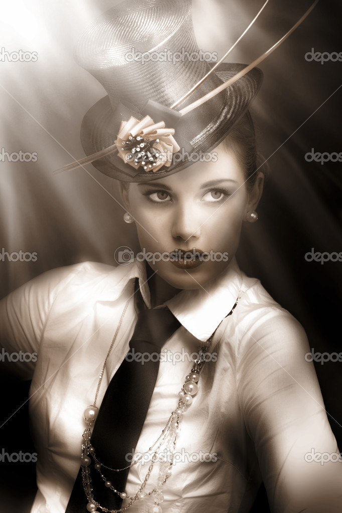 Woman actress in vaudeville costume of top-hat and tie standing lit up and illuminated under the bright lights of broadway — Stock Photo #9739610