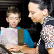 Mother And Son Consulting Menus - Stock Photo