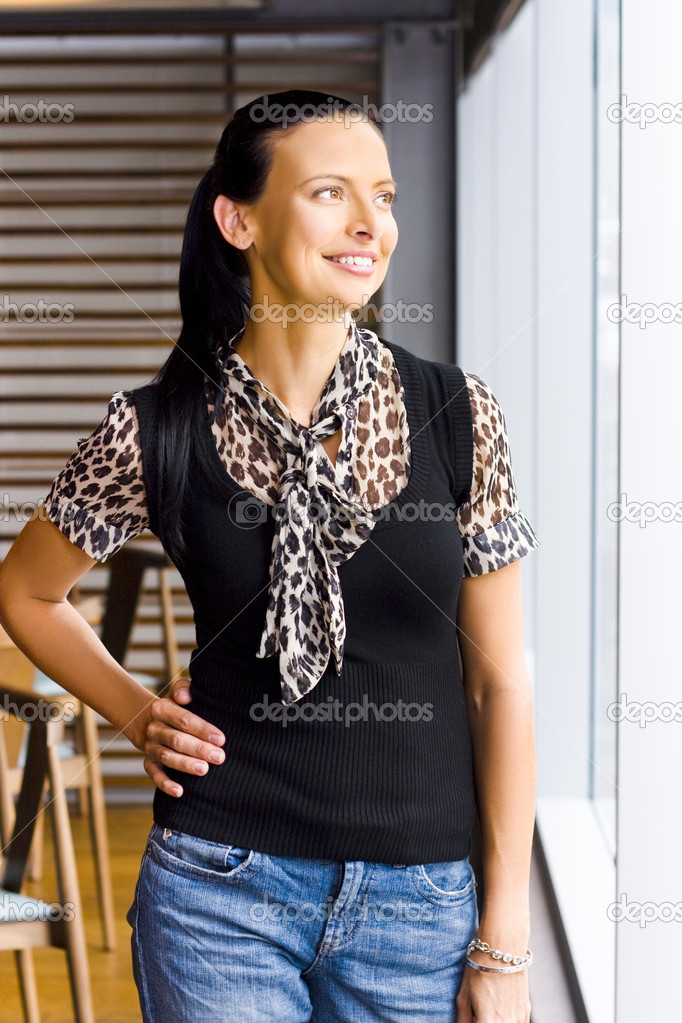 Relaxed beautiful middle-aged woman in fashionable animal print blouse and jeans standing at a window of her home looking out  Stock Photo #9762415