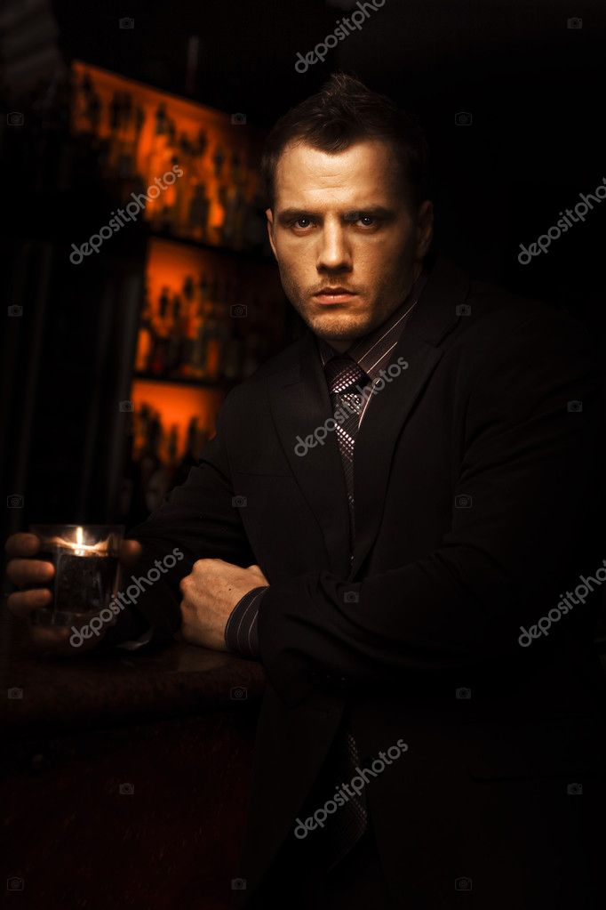 Handsome Tough Young Man With A Serious Look Standing In A Dark Bar With A Drink In A Bar Room Brawl And Fight Club Conceptual — Foto de Stock   #9764811