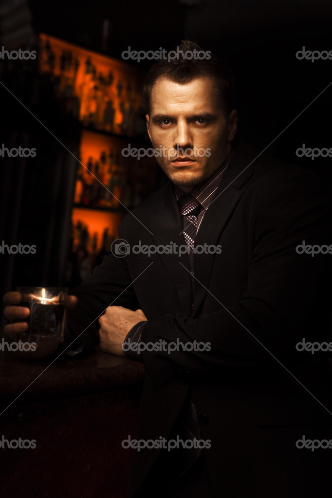Handsome Tough Young Man With A Serious Look Standing In A Dark Bar With A Drink In A Bar Room Brawl And Fight Club Conceptual — Lizenzfreies Foto #9764811