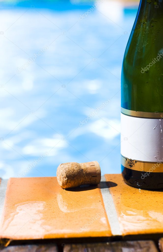 Green champagne bottle with a blank gold rimmed label and a cork standing on wet tiles alongside a sparkling blue swimming pool in a summer party concept — Stock Photo #9824387