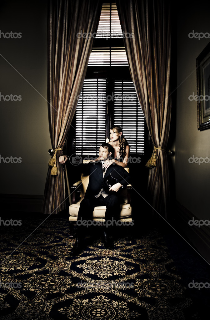 Wealthy young retro couple posing before luxurious gold curtains for a portrait in their lavish family home in a depiction of fortune, riches and wealth — Stock Photo #9846896