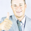 Young businessman giving thumbs up — Stock Photo