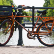 Orange bike and the canals of Amsterdam — Stok fotoğraf #7964535