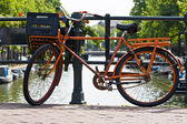 Orange bike and the canals of Amsterdam — Stock Photo