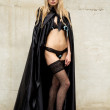 Kinky beauty in lingerie with gothic cape and mask — Stock Photo