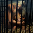 Bondage art style with beautiful nude slave girl locked in cage — Stock Photo