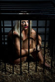 Bondage style with beautiful nude slave girl locked in cage — Stock Photo