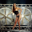 Sexy top model in lingerie on a stage with huge turbo fan behind - Stock Photo