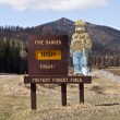 Stock Photo: Smokey Bear Sign with Burned Mountain Backdrop