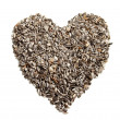Sunflower seeds background in the shape of a heart. - Stock Photo