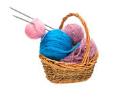 Yarn for knitting with knitting needles in a wicker basket — Stock Photo