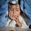 Boy reading a book under the covers with a flashlight - Foto Stock