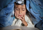 Boy reading a book under the covers with a flashlight — Stock Photo