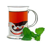 Tea in a glass holder and a sprig of lemon balm — Stock Photo
