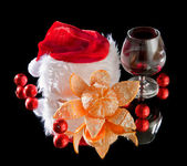 Glasses of wine, tangerine and chocolate and Santa Claus hat on a black bac — Stock Photo