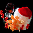 Glasses of wine, tangerine and chocolate and Santa Claus hat on a black bac - Stock Photo