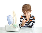 The boy looks at the thermometer. Isolate on white background — Stock Photo