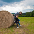 A girl and a boy pushing a round bundle of straw. — Stock Photo