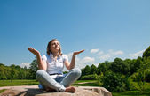 Young girl sitting on a felled tree and meditating. — Stock Photo