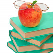 Stack of books with an apple and glasses on a white background — Stock Photo