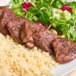 Tenderloin steaks in wine sauce with cadamon and kuskus groats — Stock Photo
