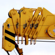 Yellow industrial utillity crane hook against electric pole and blue sky - Stock Photo