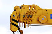 Yellow industrial utillity crane hook against electric pole and blue sky — Stock Photo