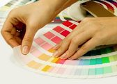 Woman selecting color from Pantone swatches book — Stock Photo