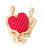 Wooden dolls hold heart — Stock Photo