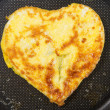 Heart shaped scrambled eggs - Stock Photo