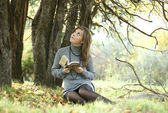 The beautiful girl sits under a tree with the book — Stock Photo