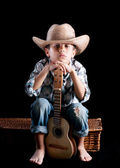 A boy wearing a hat with a guitar on a black background — Stock Photo